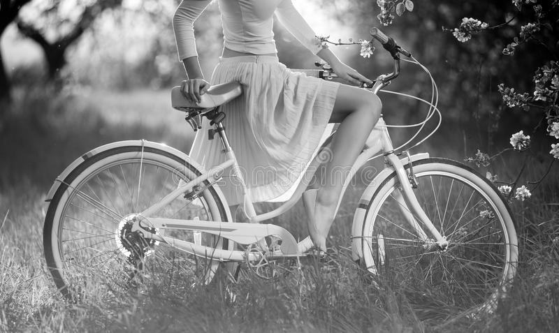 Beautiful female cyclist with retro bicycle in the spring garden. Close-up of graceful bend leg of pretty woman in white dress sitting on bicycle. Black and stock image