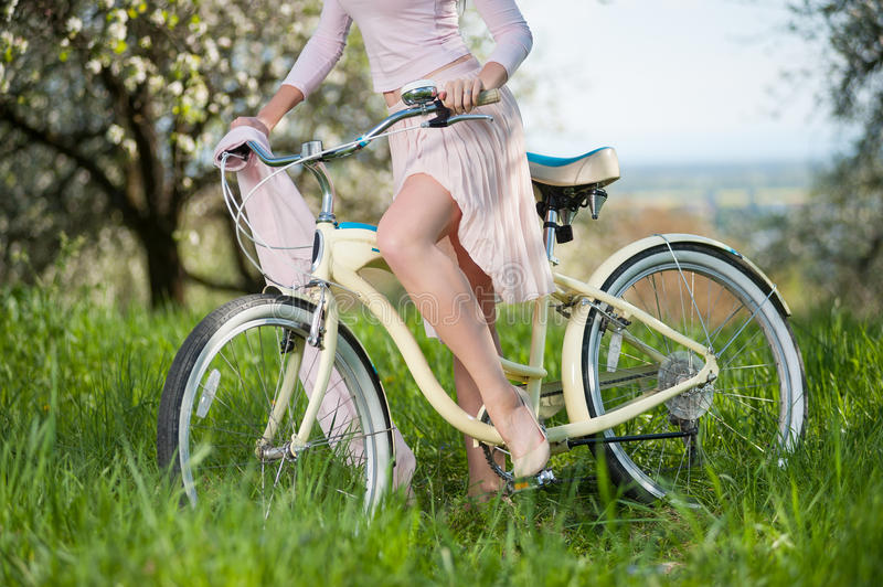 Beautiful female cyclist with retro bicycle in the spring garden. Close-up of perfect bend leg of pretty girl in white dress sitting on vintage bike against stock photos