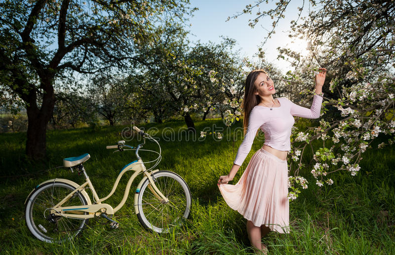 Beautiful female cyclist with retro bicycle in the spring garden. Happy girl holding hands flying light skirt near blooming trees and vintage white bicycle stock photography