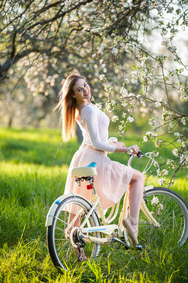 Beautiful female cyclist with retro bicycle in the spring garden. Happy woman in nice dress enjoying riding bicycle near blossoming tree in the ray of sunshine stock photo