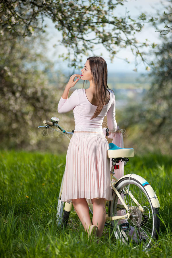 Beautiful female cyclist with retro bicycle in the spring garden. Brunette female wearing a nice white dress with bicycle standing with her back and turned to stock images