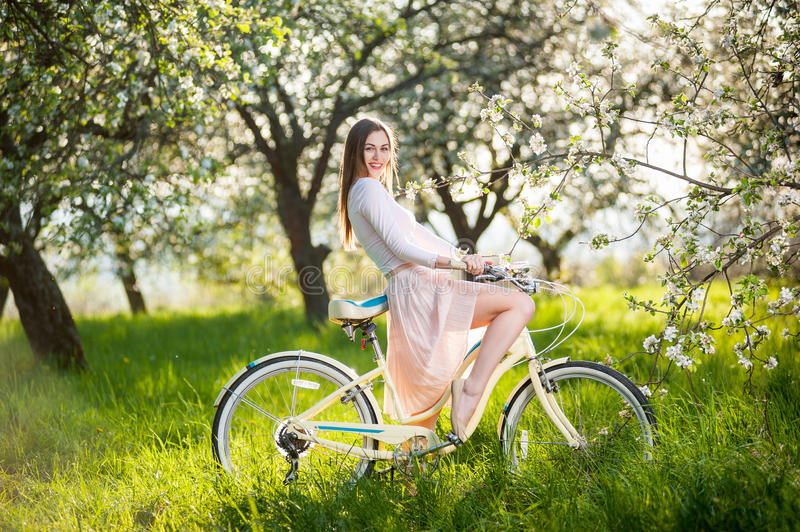 Beautiful female cyclist with retro bicycle in the spring garden. Smiling female enjoying a retro bike in the lush green grass near blossoming tree in the ray of royalty free stock image