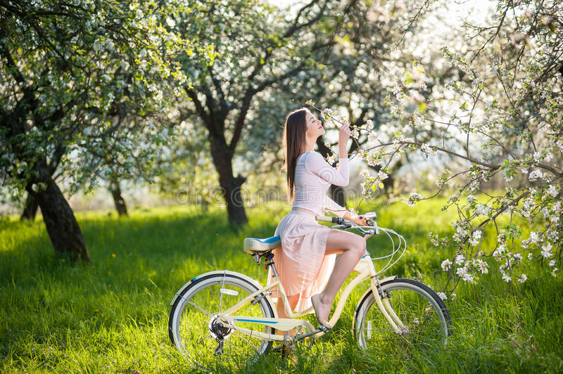 Beautiful female cyclist with retro bicycle in the spring garden. Woman with a retro bicycle in the lush green grass enjoying a blossoming tree in the ray of stock photo