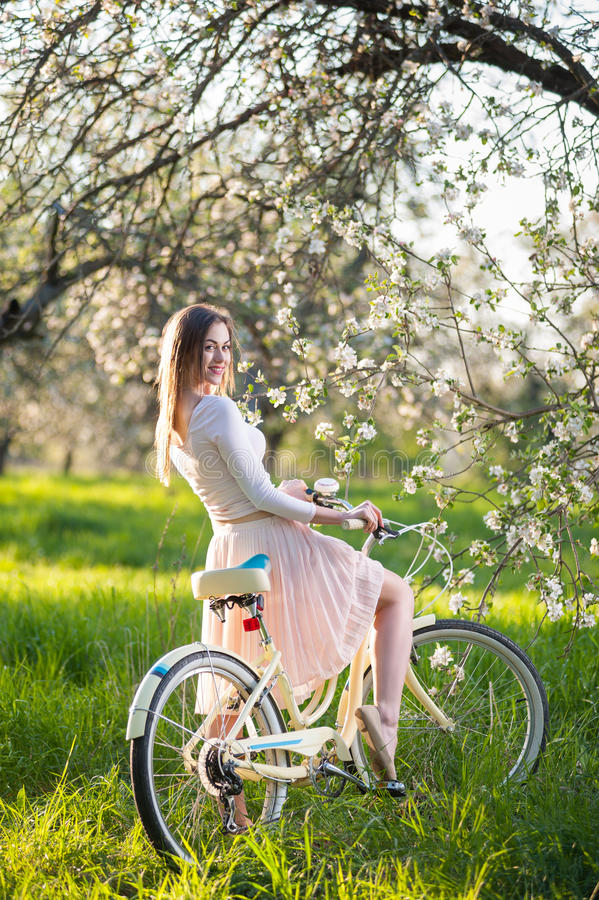 Beautiful female cyclist with retro bicycle in the spring garden. Beautiful woman in nice dress riding vintage bicycle in the lush green grass near blossoming stock photography
