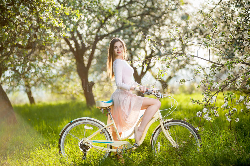 Beautiful female cyclist with retro bicycle in the spring garden. Beautiful woman riding a bicycle in the lush green grass near blossoming tree in the ray of royalty free stock photo