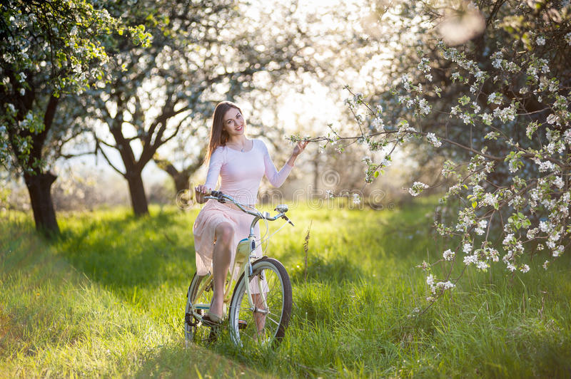 Beautiful female cyclist with retro bicycle in the spring garden. Young girl with long brunette hair wearing light dress riding a retro white bike holds a hand a royalty free stock images
