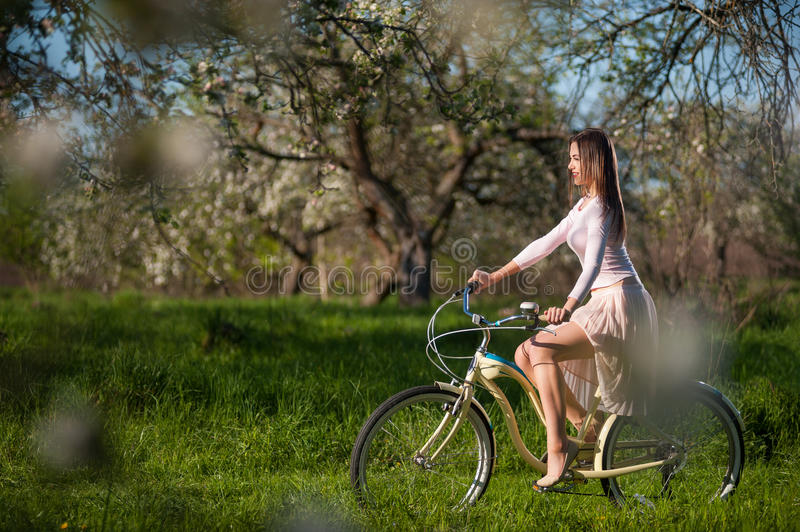 Beautiful female cyclist with retro bicycle in the spring garden. Young woman with long brunette hair wearing light dress riding a vintage white bicycle, under royalty free stock photo