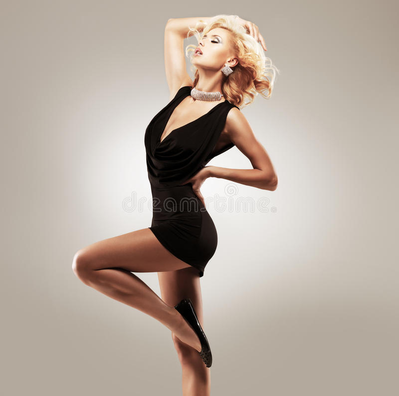 Beautiful female dancer in black dress. Posing at studio stock photography