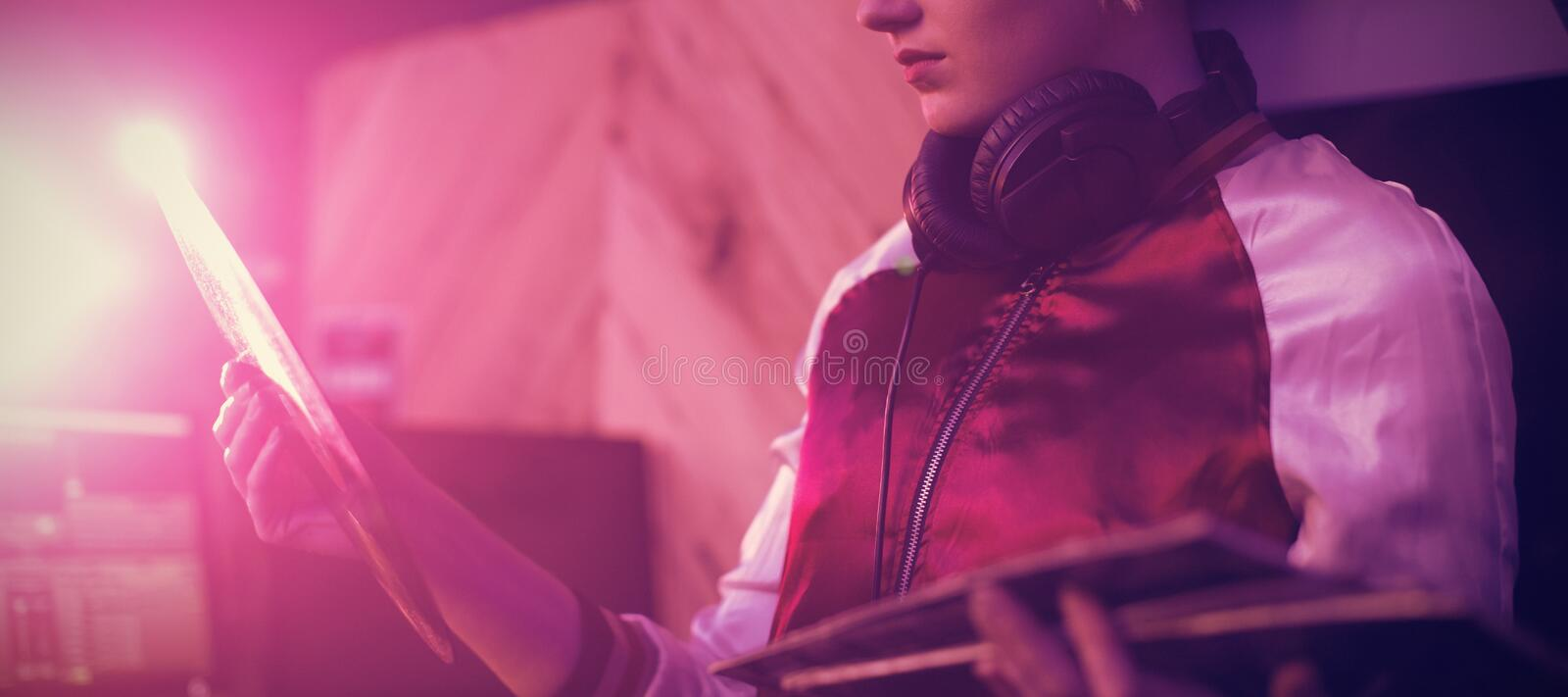 Female dj holding a vinyl disc record in bar. Beautiful female dj holding a vinyl disc record in bar royalty free stock photography