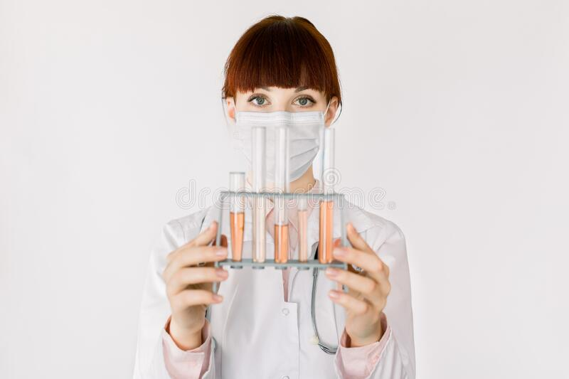 Beautiful female doctor, biotechnology scientist, chemist or pharmacist, wearing white coat, holding set of glass lab. Tubes with red liquid, standing on white stock images