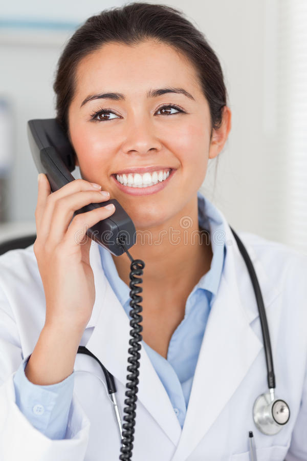 Beautiful female doctor on the phone and posing. In her office royalty free stock images