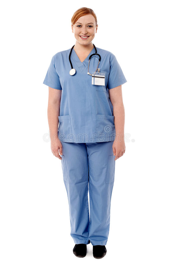 Beautiful female doctor standing against white. Full length of smiling female doctor with stethoscope stock photo