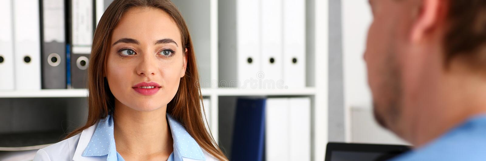 Beautiful female doctor talk with male visitor stock image