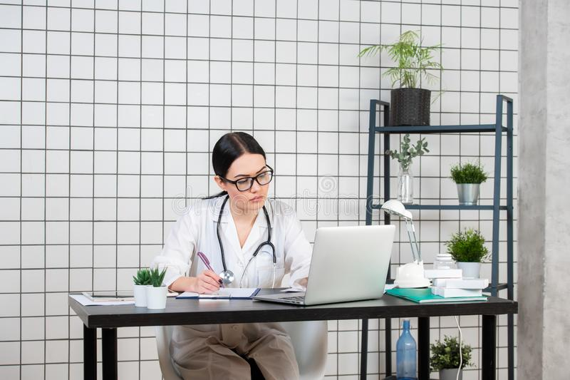 Beautiful female doctor writing while using laptop at desk in clinic royalty free stock photo