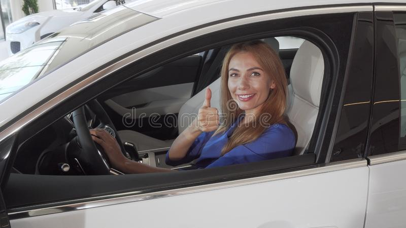 Beautiful female driver smiling to the camera sitting in a new car at the dealership. Charming businesswoman choosing new auto to buy, showing thumbs up stock image