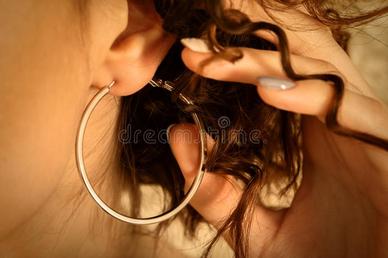 Ear with curl hair. Beautiful female ear with large earring and hand in curl hairs stock image