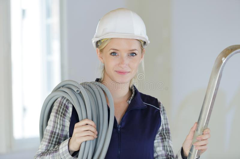 Beautiful female electrician holding cable royalty free stock photo