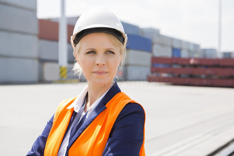 Beautiful female engineer looking away in shipping yard royalty free stock photo