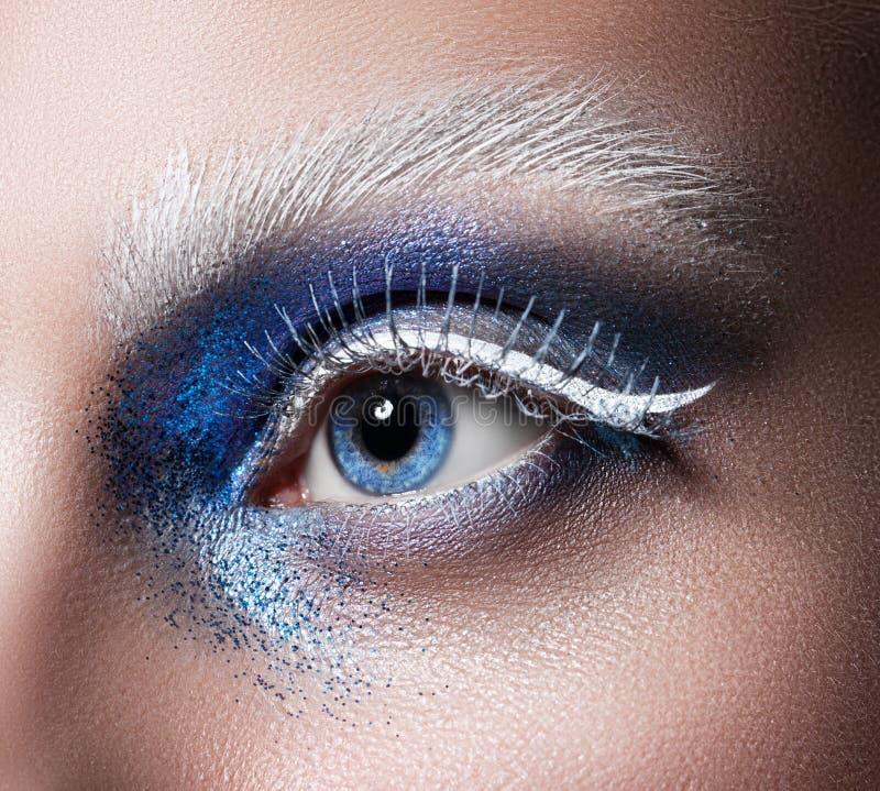 Beautiful female eye close-up. Blue eyes. Creative makeup stock images