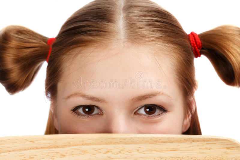 Beautiful female face with funny ponytails tied by red scrunchies hidden behind wooden cutting board stock image