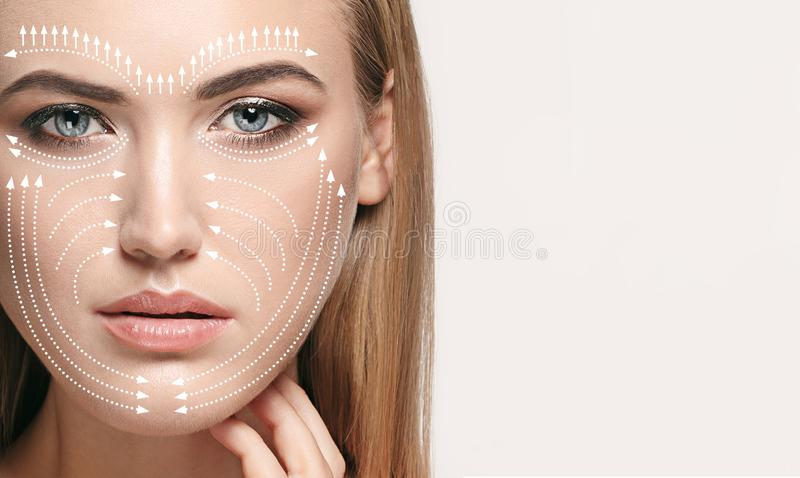 Beautiful female face, concept of skincare and lifting. Beautiful female face  on grey background. Concept of bodycare, cosmetics, skincare and lifting stock photo