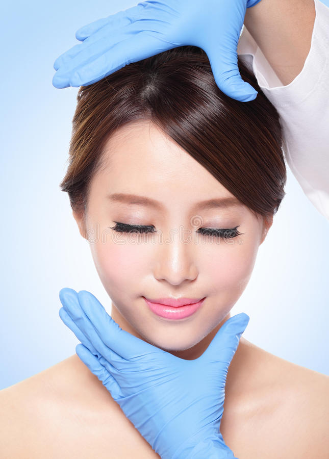 Beautiful female face with Plastic surgery glove stock image