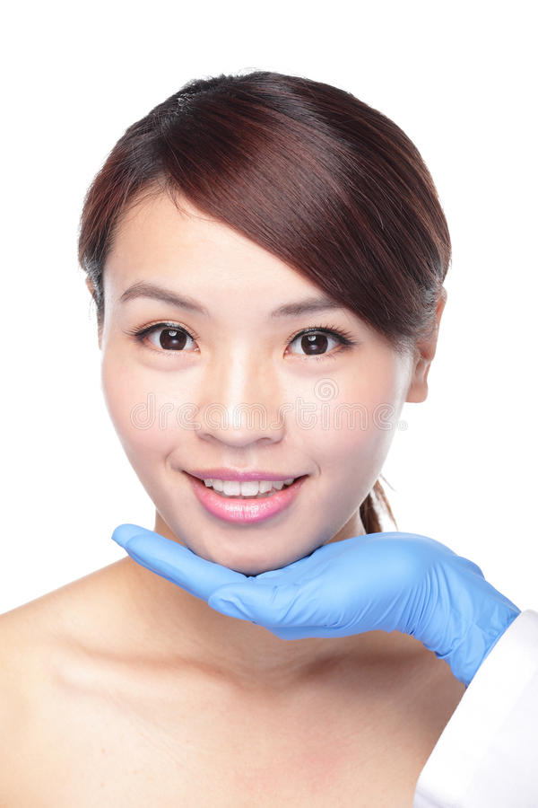 Beautiful female face with Plastic surgery glove. Plastic surgery touching the head of a beautiful female face, concept for micro plastic surgery, asian beauty stock image