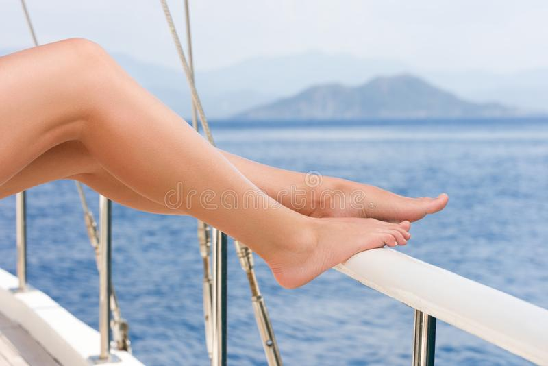 Beautiful female feet against the sea cruise landscape. Rest on a yacht royalty free stock photography