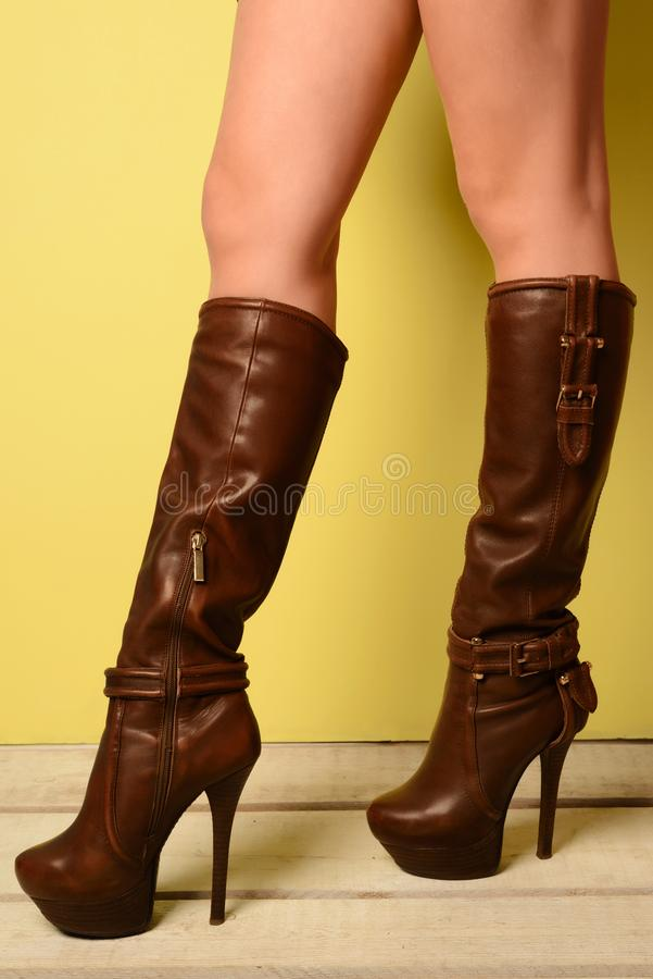 Beautiful female feet in brown high-heeled boots royalty free stock photos