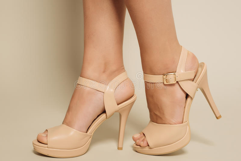 Beautiful female feet in brown sandals with high heels royalty free stock images