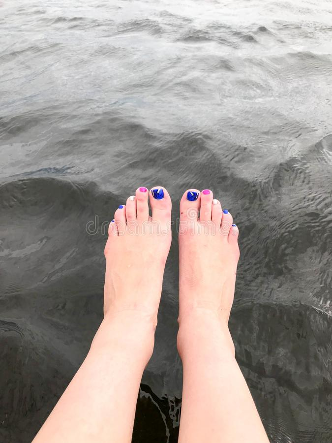 Beautiful female feet the feet with fingers with a multi-colored fashion manicure are dropped dangling into cold dark black water stock photos