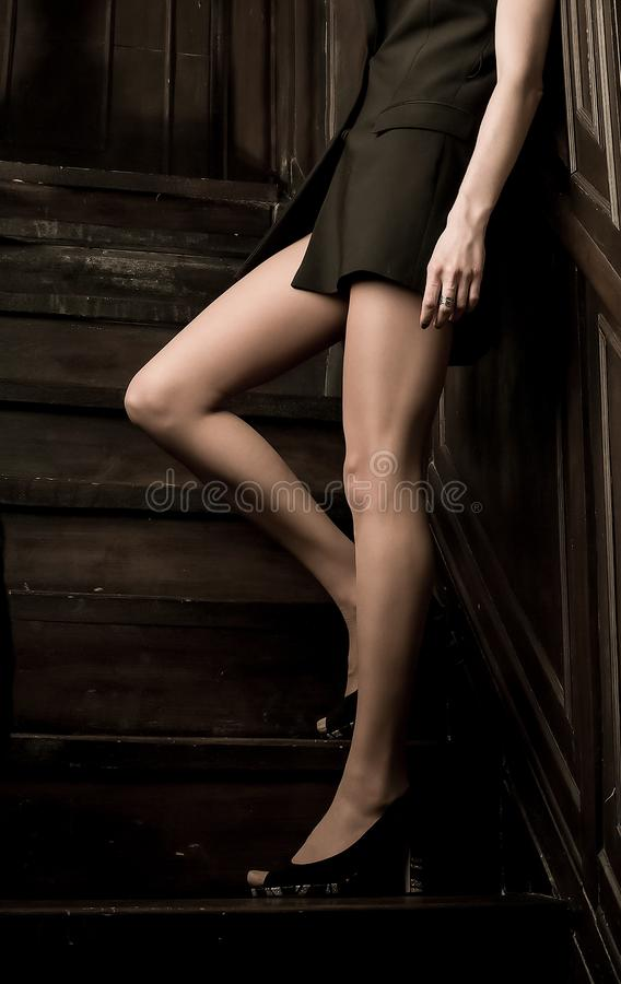Beautiful female feet in high heels stand on a dark staircase on a dark background stock photo