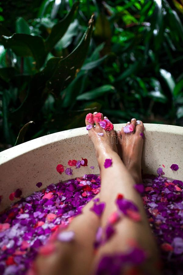 Beautiful female feet in outdoor bath with tropical flowers.Spa, stock photography