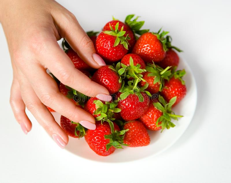 Female fingers with a manicure take a strawberry berry from the royalty free stock photography
