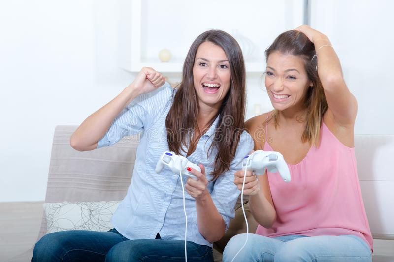 Beautiful female friends having fun while playing video games stock photo