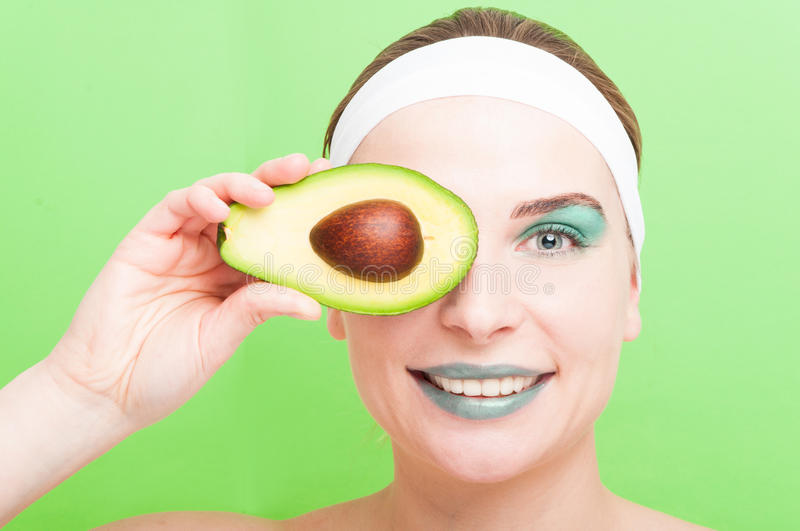 Beautiful female with half of fresh avocado. Taking care of her skin in natural way isolated on green background royalty free stock photography