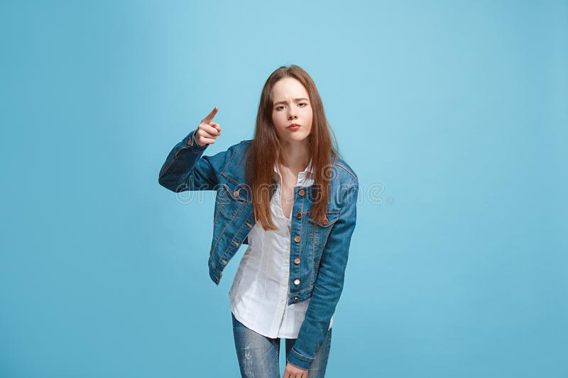 Beautiful female half-length portrait on blue studio backgroud. The young emotional teen girl stock photography