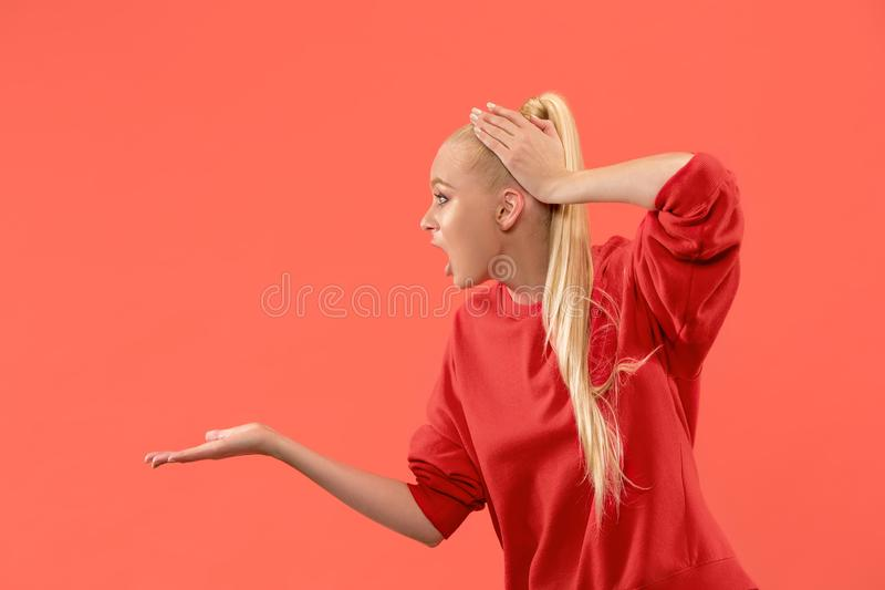 Beautiful female half-length portrait isolated on coral studio backgroud. The young emotional surprised woman. Argue, arguing concept. Beautiful female half stock photo