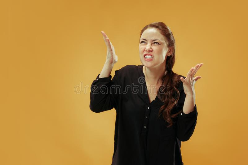 Beautiful female half-length portrait isolated on gold studio backgroud. The young emotional surprised woman stock photo