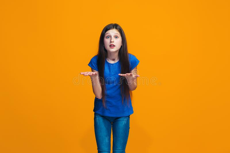 Beautiful female half-length portrait on orange studio backgroud. The young emotional teen girl. Argue, arguing concept. Profile of beautiful female half-length royalty free stock photos