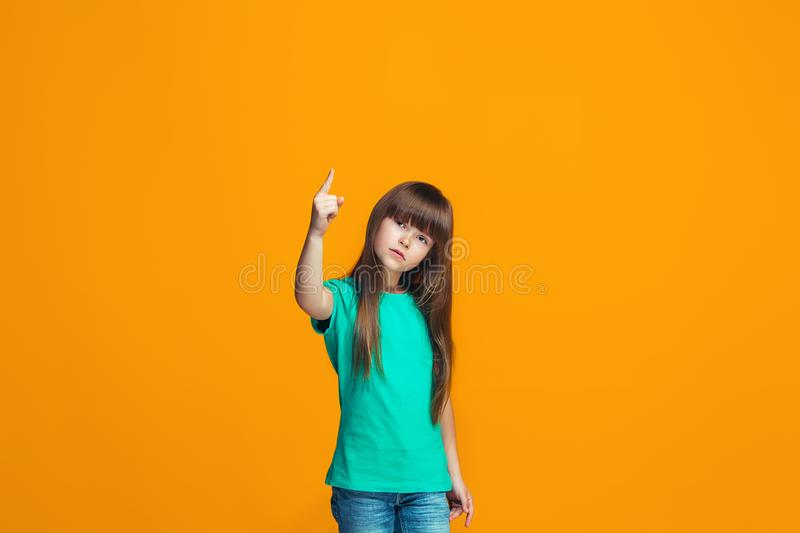 Beautiful female half-length portrait on orange studio backgroud. The young emotional teen girl. Argue, arguing concept. Profile of beautiful female half-length stock images