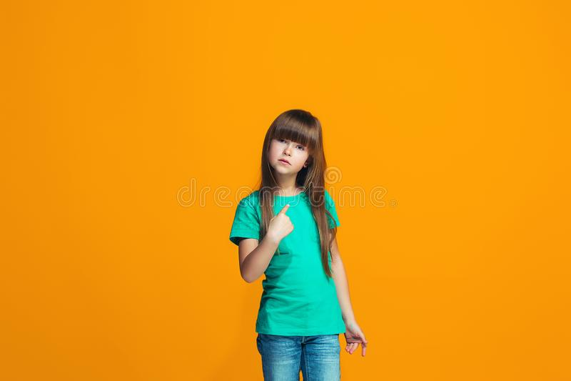 Beautiful female half-length portrait on orange studio backgroud. The young emotional teen girl. Argue, arguing concept. Profile of beautiful female half-length royalty free stock image