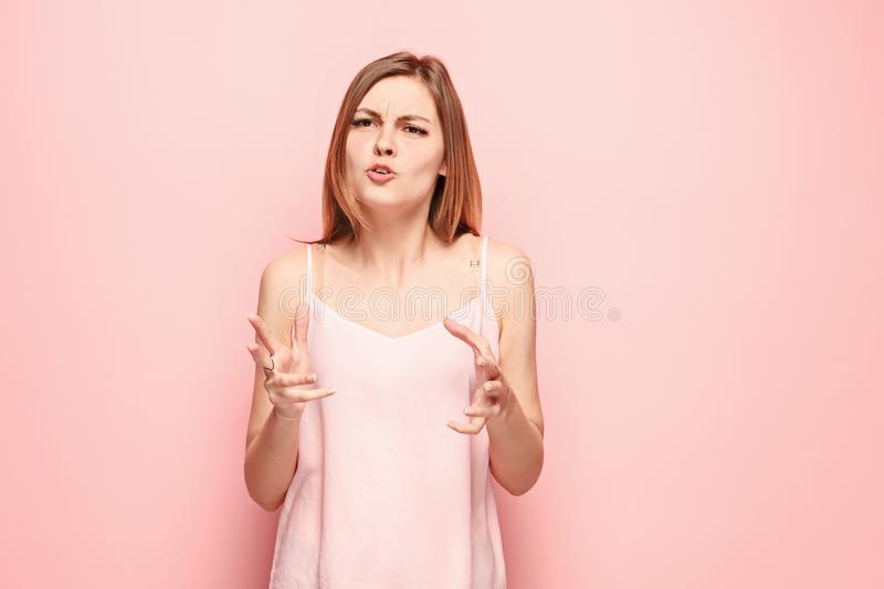Beautiful female half-length portrait on pink studio backgroud. The young emotional surprised woman. Argue, arguing concept. Beautiful female half-length royalty free stock photography