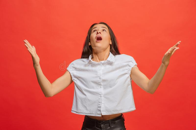 Beautiful female half-length portrait on red studio backgroud. The young emotional surprised woman. Argue, arguing concept. Beautiful female half-length portrait royalty free stock photo