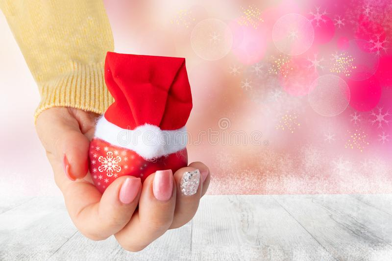 Beautiful female hand with christmas nail design. Hand with elegant pink nail manicure holding a red christmas decoration ball wi royalty free stock photo