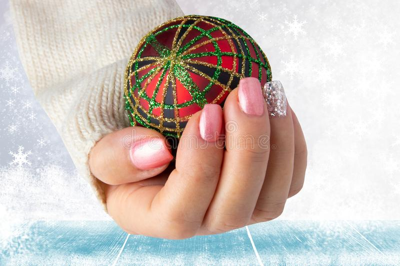 Beautiful female hand with christmas nail design. Hand with elegant pink nail manicure holding a red christmas decoration ball. S stock photos