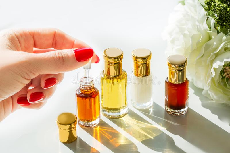 A Beautiful Female Hand Holding The Dropper Of The Essential Aromatic Oils In Orange Yellow White & Brown Colors Used For Spa Mas stock images
