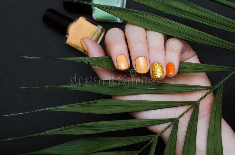 Beautiful female hand with yellow nail design with glitter. stock photo