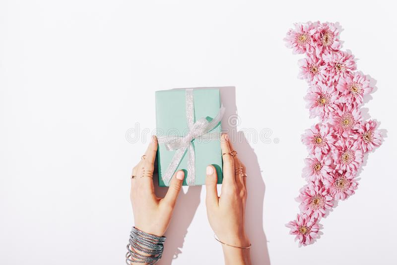 Beautiful female hands hold the blue box with a gift royalty free stock photo