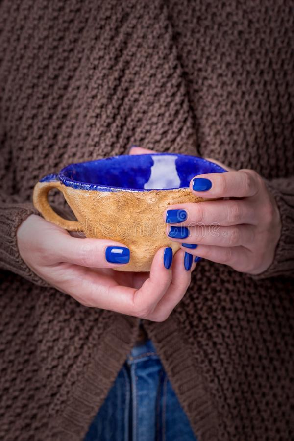 Beautiful female hands holding brown clay cup with blue enamel. Manicure with blue nail polish. Cozy concept royalty free stock images
